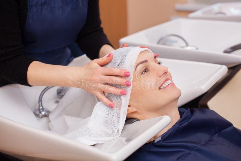 De kapper wast de shampoo van het haar aan een jong meisje royalty-vrije stock afbeeldingen