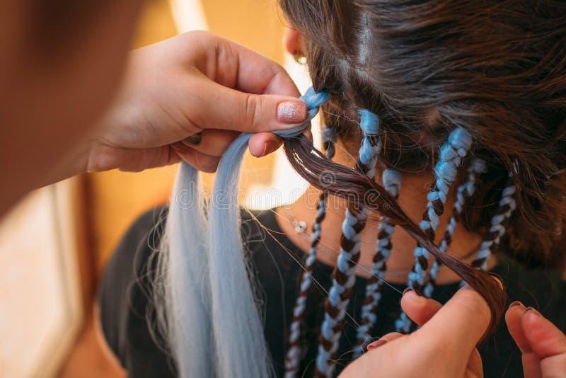 De kapper weeft vlechten met kanekalonmateriaal aan jong meisjeshoofd, makend creatief kapsel met dikke vlechten of vlechten royalty-vrije stock afbeelding