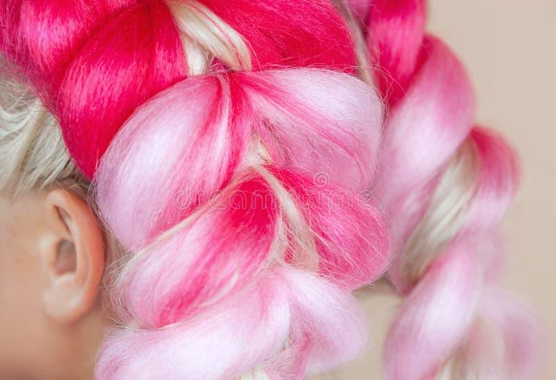 De kapper weeft vlechten met roze kanekalons mooi blonde royalty-vrije stock afbeeldingen