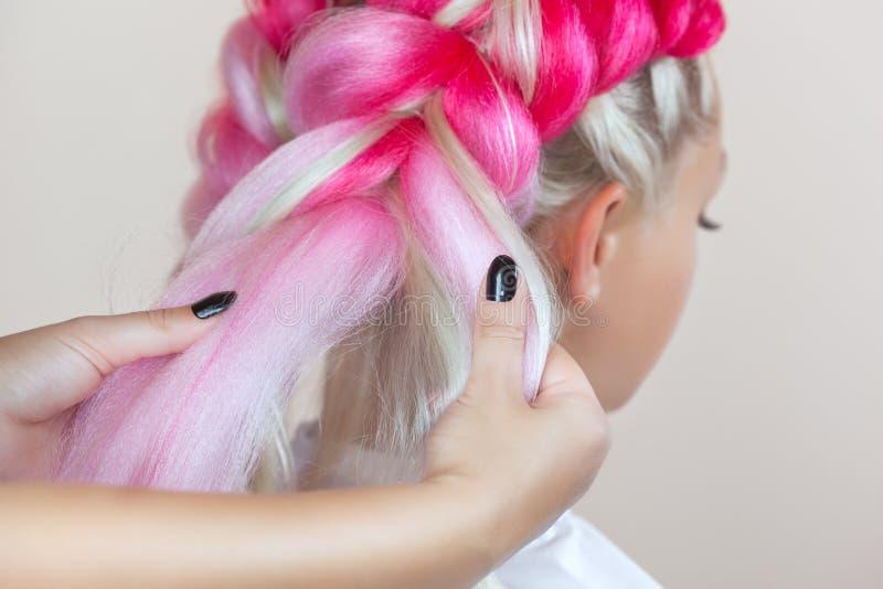 De kapper weeft vlechten met roze kanekalons mooi blonde royalty-vrije stock foto's