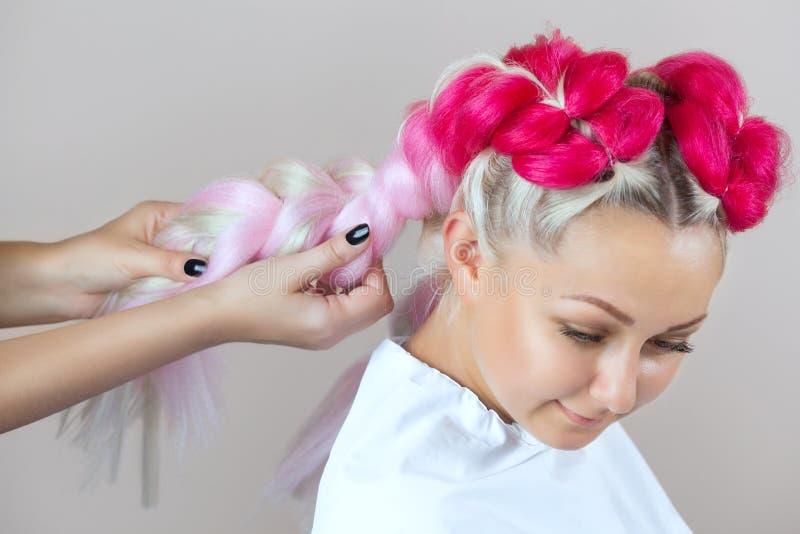 De kapper weeft vlechten met roze kanekalons mooi blonde stock foto