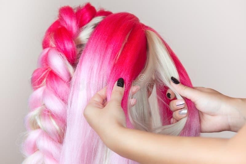 De kapper weeft vlechten met roze kanekalons mooi blonde stock fotografie