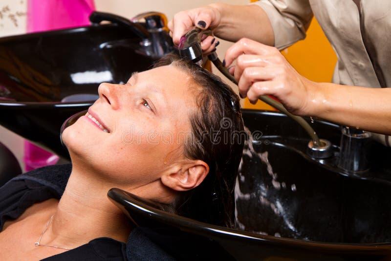 De kappers overhandigen was het haar van de vrouwelijke klant stock fotografie