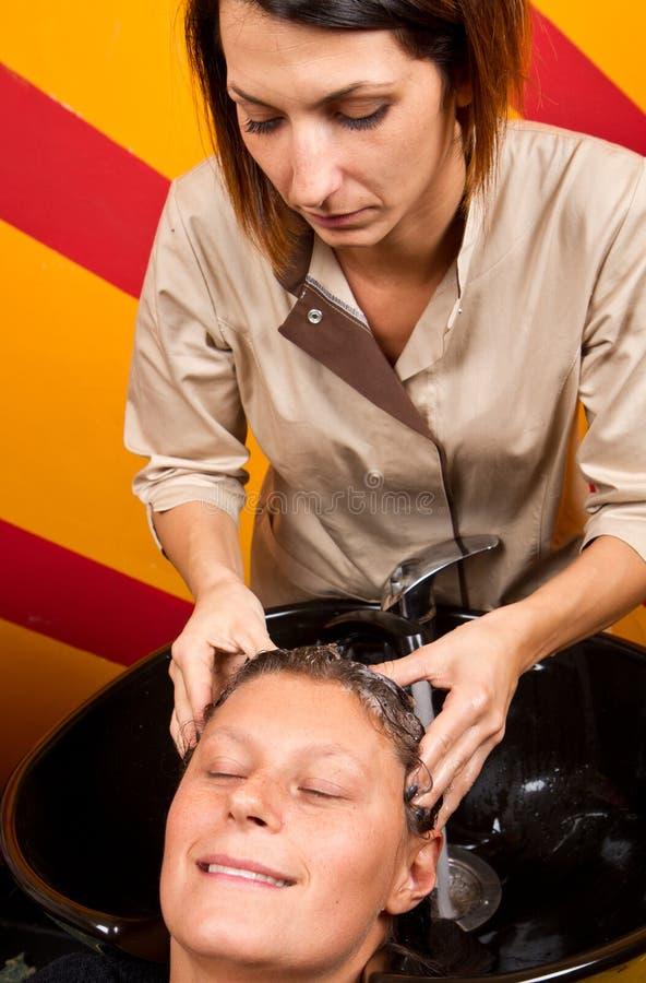 De kappers overhandigen was het haar van de vrouwelijke klant in salon royalty-vrije stock foto