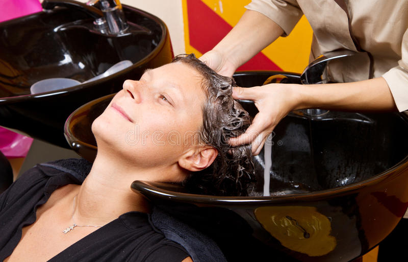 De kappers overhandigen was het haar van de vrouwelijke klant in salon stock foto
