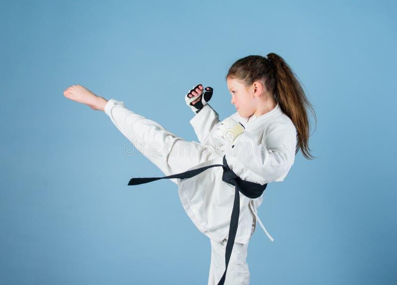De karate geeft gevoel van vertrouwen Sterk en zeker jong geitje Zij is gevaarlijk Meisje weinig kind in witte kimono met stock foto