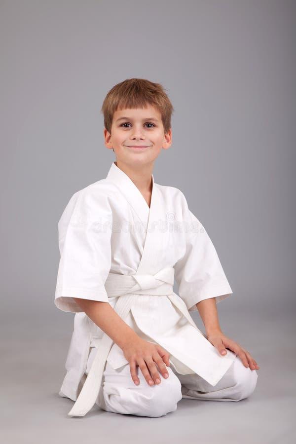 De karatejongen in witte kimono zit royalty-vrije stock foto