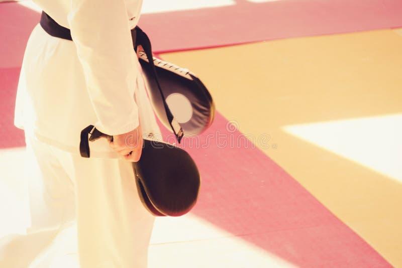 De karatetrainer in kimono met het schoppen richt stootkussen in van hem indient de gymnastiek tijdens opleiding royalty-vrije stock foto
