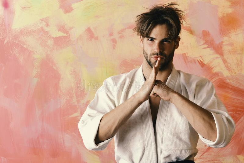 De karatevechter met sterk lichaam toont het traditionele vechtsporten begroeten Japans karateconcept De kerel stelt in wit stock afbeeldingen