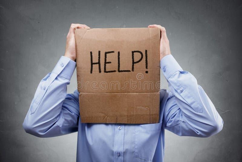 De kartondoos op zakenmanhoofd vraagt om hulp royalty-vrije stock afbeeldingen