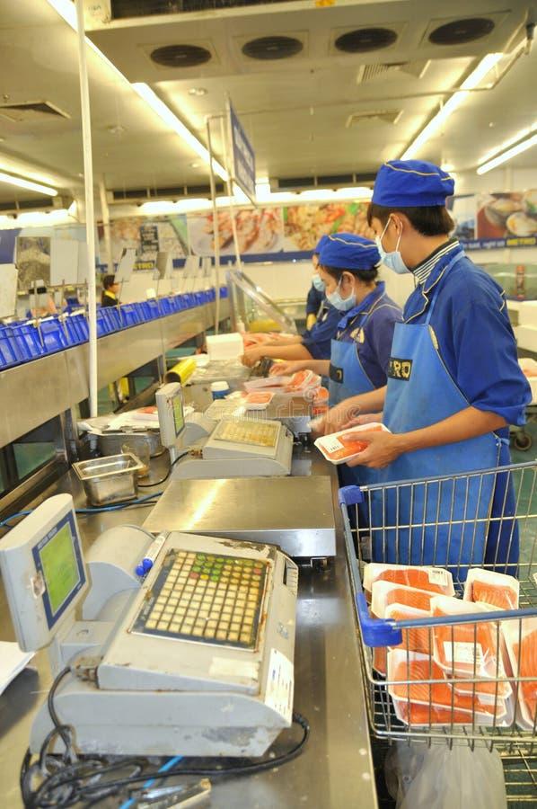 De kassiers werken hard in zeevruchtencabines in een moderne supermarkt in Vietnam stock afbeeldingen
