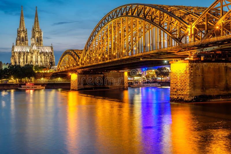 De Kathedraal van Keulen en Hohenzollern-Brug bij nacht, Duitsland stock fotografie