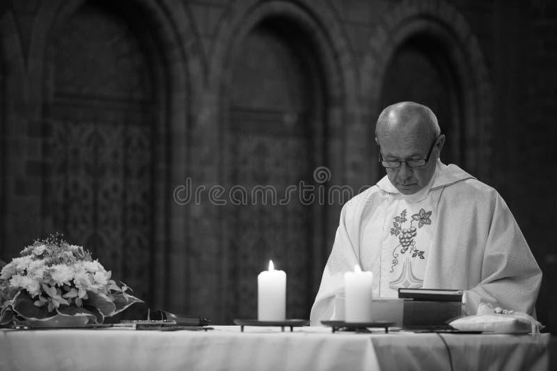 De katholieke priester leest heilige bijbel stock fotografie