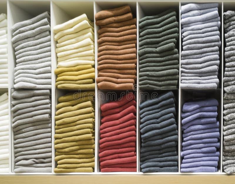 De katoenen T-shirt vouwde keurig in de toonzaal, de Kleurrijke die kleren in het kabinet wordt gevouwen, de Kleurrijke keurig ge royalty-vrije stock foto's