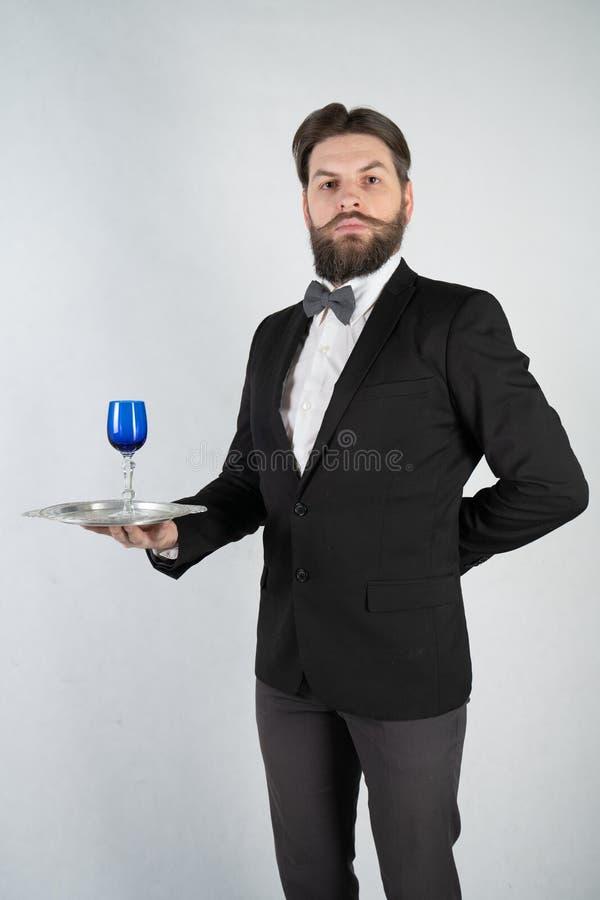 De Kaukasische bediende met een baard in een formeel pak bevindt zich met een staaldienblad in zijn hand en een glas wijn op een  stock fotografie