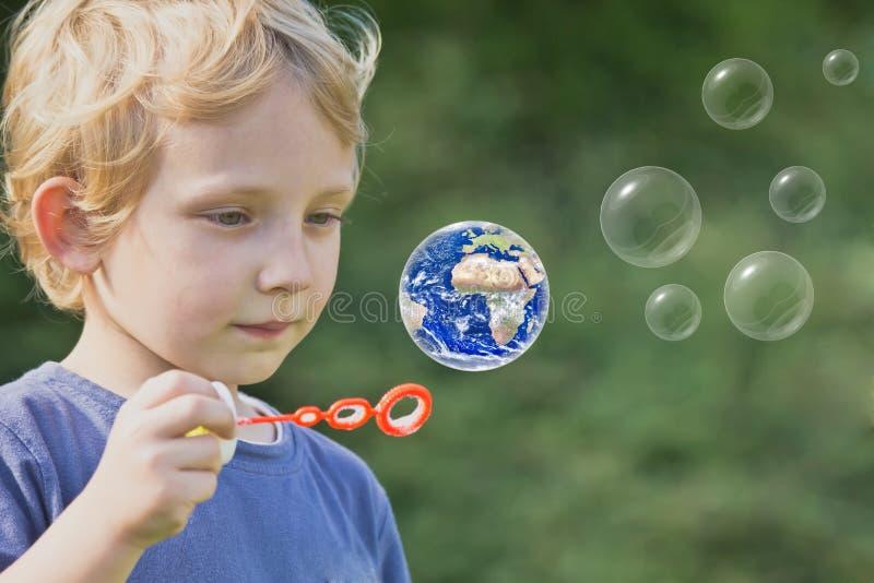 De Kaukasische blonde jongen speelt met zeepbels stock afbeelding
