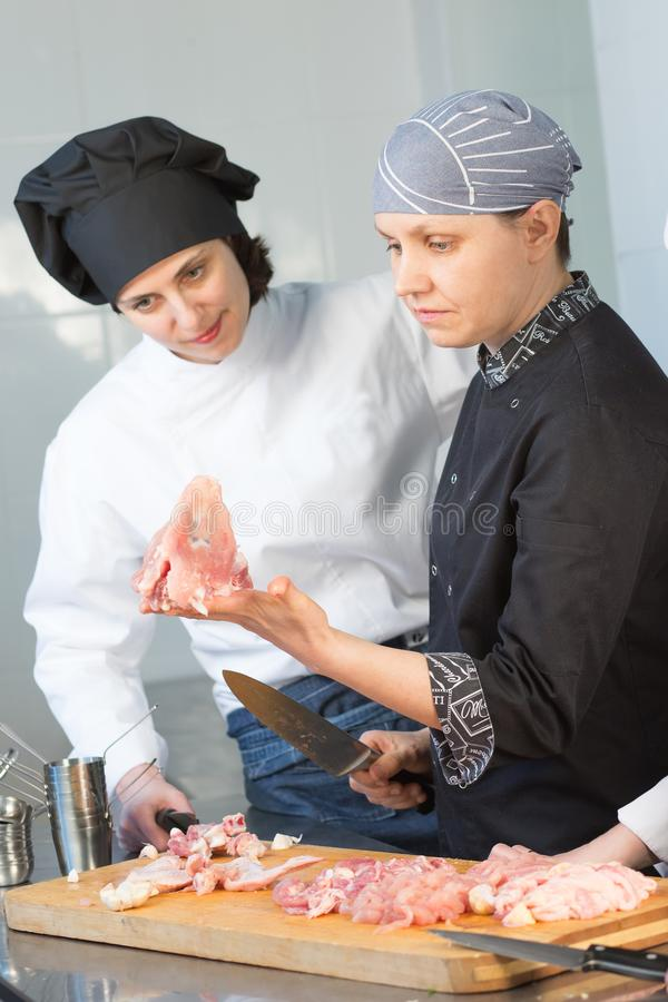 De Kaukasische chef-kok onderwijst stagiair om een kip te snijden Hoofdklasse op de achtergrond van de keuken royalty-vrije stock afbeelding
