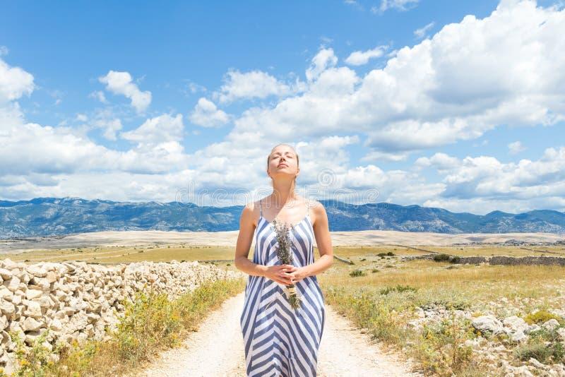 De Kaukasische jonge vrouw in de holdingsboeket van de de zomerkleding van lavendel bloeit het genieten van van zuivere Mediterra royalty-vrije stock afbeelding