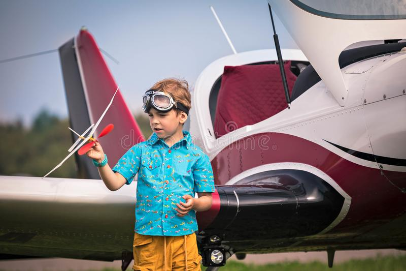 De Kaukasische jongen in gele borrels, een blauw overhemd en in luchtvaartpunten houdt het stuk speelgoed vliegtuig en h in hand stock afbeeldingen