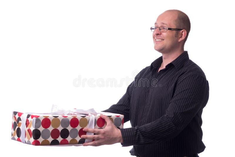 De Kaukasische kerel geeft een gift die op wit wordt geïsoleerd royalty-vrije stock afbeelding