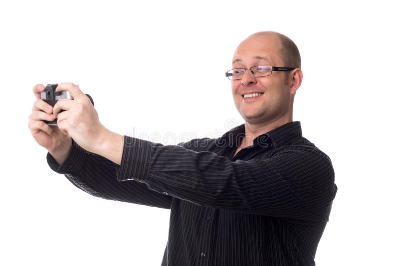 De Kaukasische kerel neemt een beeld van zich gebruikend een oude die camera op wit wordt geïsoleerd stock afbeelding