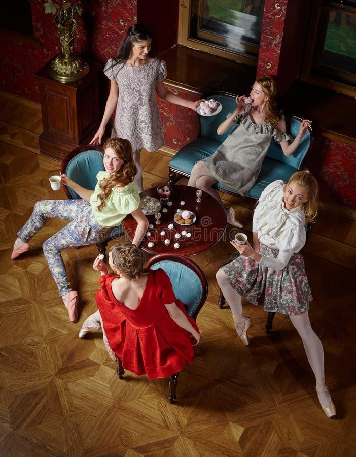 De Kaukasische manier vrolijke ballerina's in stellen het drinken thee stock foto's