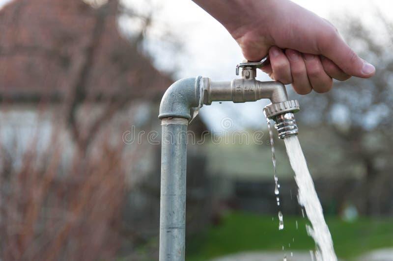 Download De Kaukasische Mannelijke Hand Opent De Kraan Van Het Tuinwater Stock Foto - Afbeelding bestaande uit tuin, flowing: 114226908