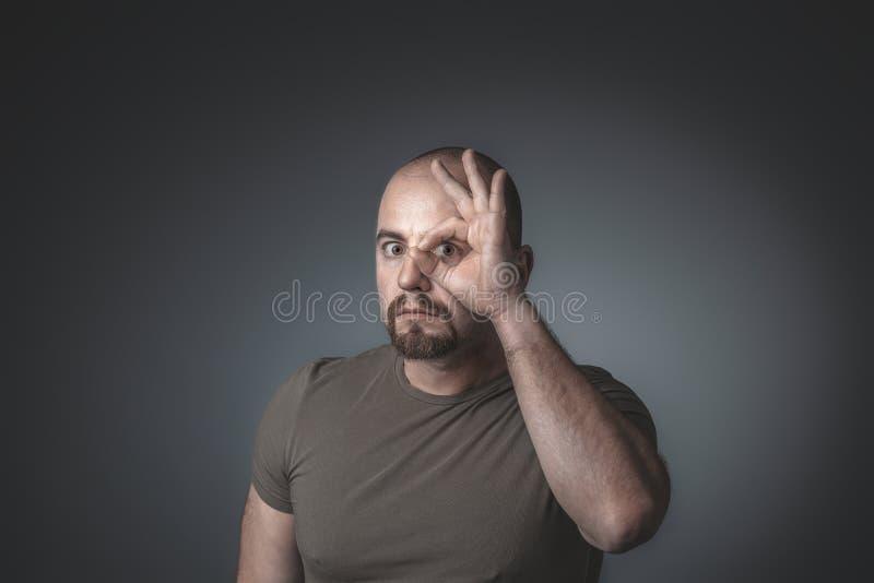De Kaukasische mens kijkt door zijn vingers die in een cirkel worden gesloten stock fotografie