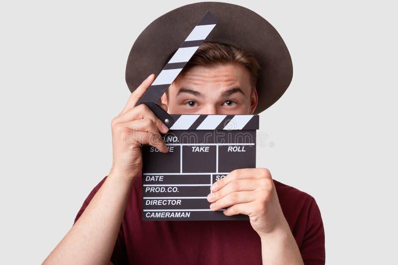 De Kaukasische succesvolle mannelijke producent kijkt door oprnrd clapperboard, werkt bij de filmproductie, draagt hoed en toeval stock afbeeldingen