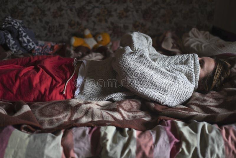 De Kaukasische vrouw die haar gezicht met sweater sluiten legt op alleen bed stock foto