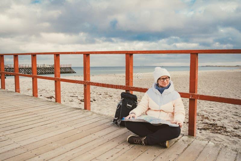 De Kaukasische vrouw in hoed en jasje met rugzak in de winter zit op houten pijler op strand dichtbij Noordzee De toerist van Den stock fotografie