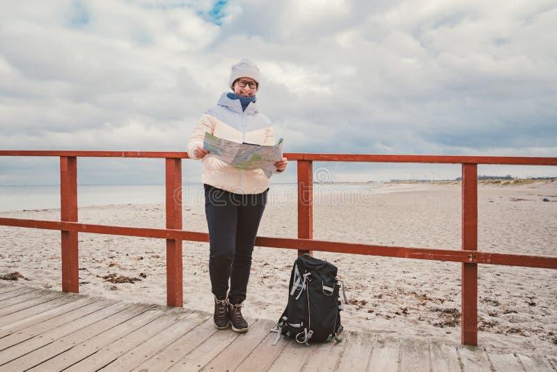 De Kaukasische vrouw in hoed en jasje met rugzak in de winter zit op houten pijler op strand dichtbij Noordzee De toerist van Den royalty-vrije stock afbeelding