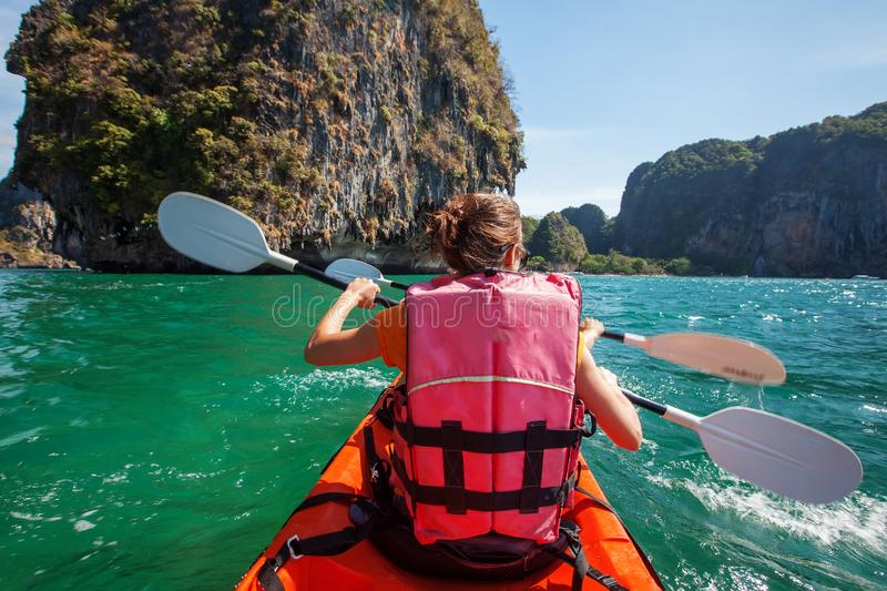 De Kaukasische vrouw kayaking in overzees in Thailand stock foto