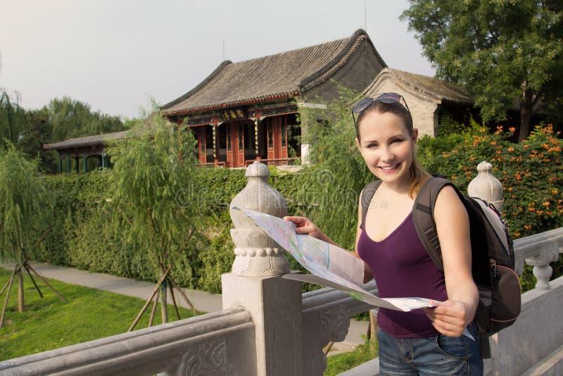 De Kaukasische vrouw met kaart en de rugzak reizen in China royalty-vrije stock afbeelding