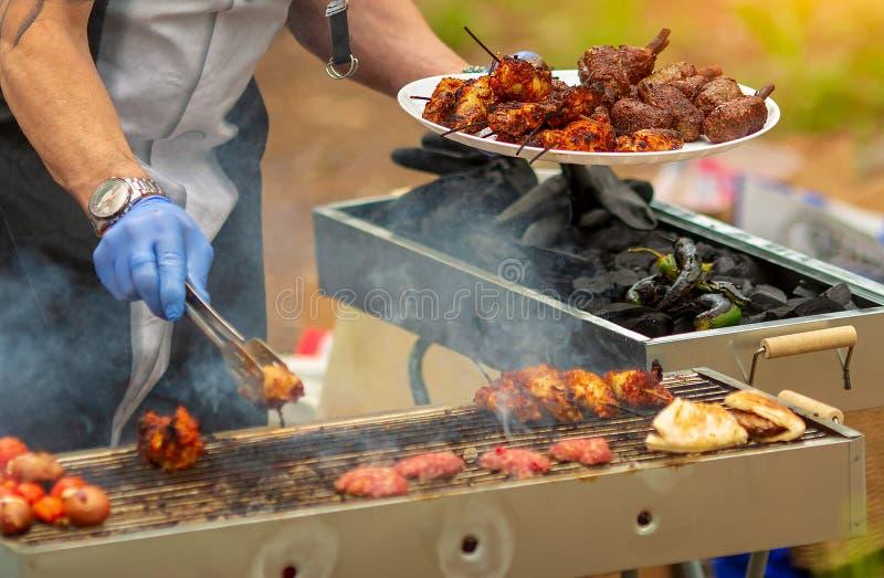 De kebab van mensenkoks op de grill in openlucht stock fotografie