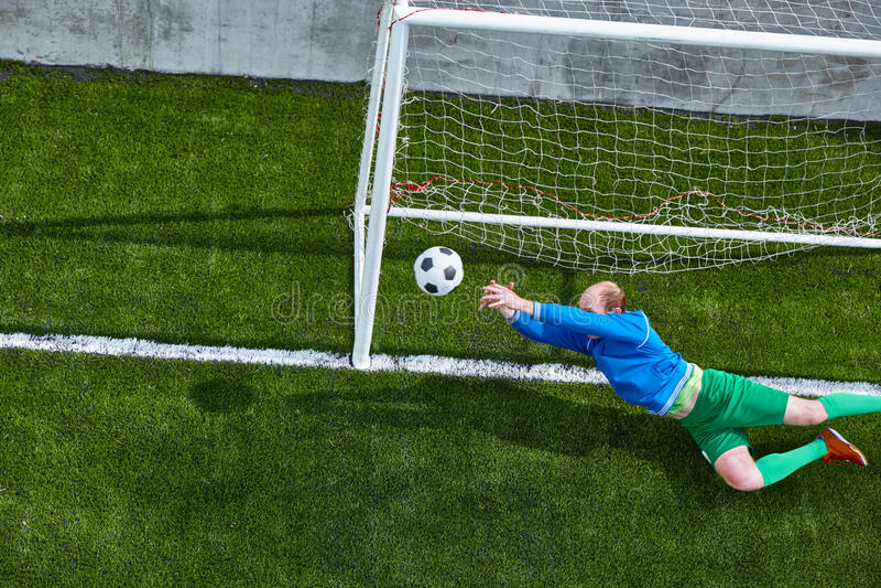 De keeper die van de voetbalvoetbal het duiken maken spaart stock foto's
