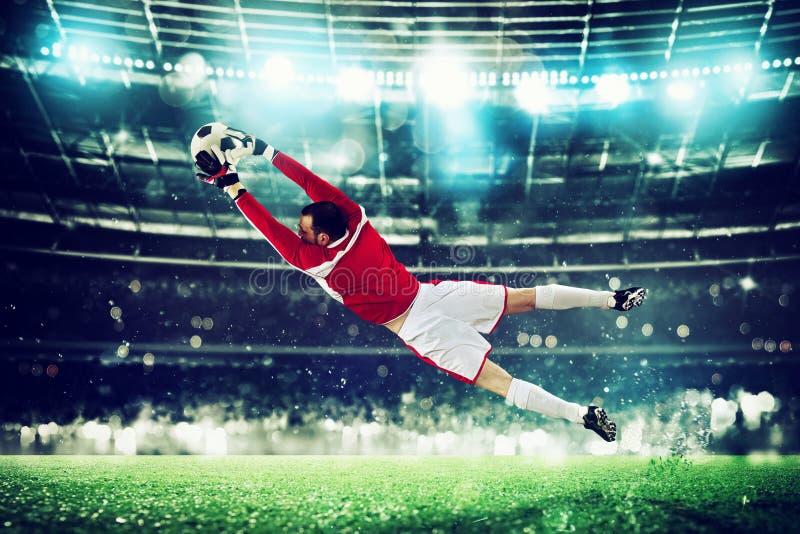 De keeper vangt de bal in het stadion tijdens een voetbalspel stock fotografie