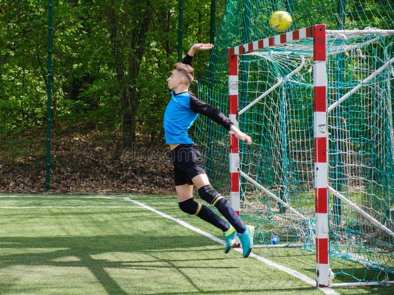 De keeper vangt de bal De stadion goalie sporten spelen grondspel, de bewaardersmens van het grasvoetbal, outdoorsc ompetition, royalty-vrije stock foto