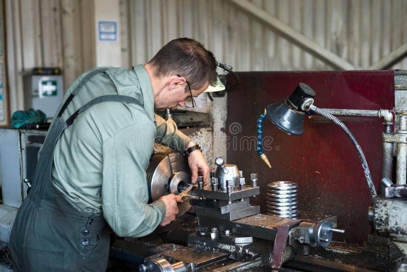 De keerder werkt op een mechanische draaibank De draaiende werken, metaalverwerking door knipsel royalty-vrije stock foto's