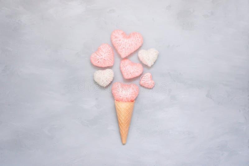 De kegel van de roomijswafel met roze en wit draadhart op grijze cementachtergrond De groetkaart van de valentijnskaartendag met  stock foto