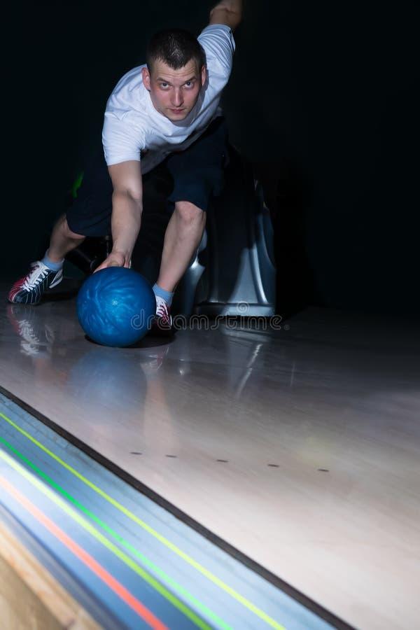 De kegelenspeler maakt een blauwe bal bewegen zich, close-up royalty-vrije stock foto's
