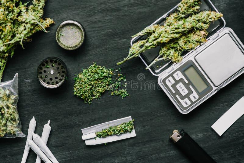 De kegels van marihuana bloeit op schalen, molen en verscheurde cannabisverbinding en een pakket van onkruid op een zwarte houten