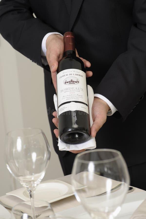 De kelner die van de wijn een fles rode wijn voorstelt stock afbeelding