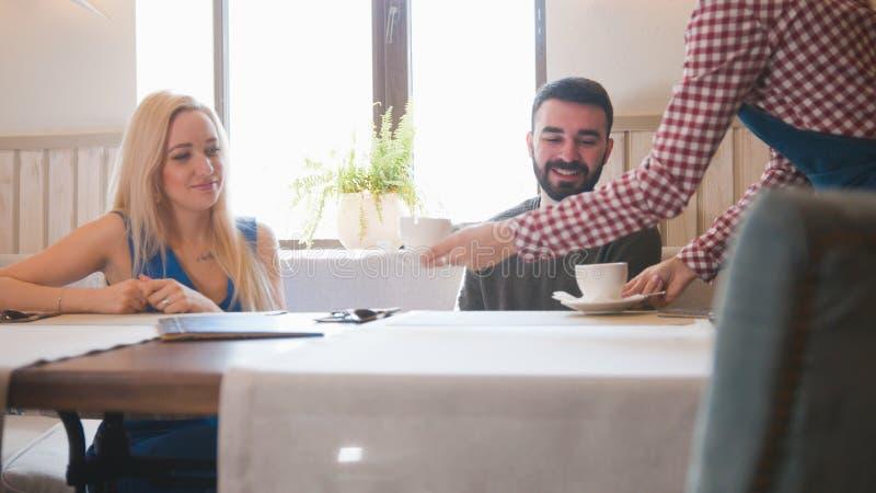 De kelner in koffie brengt thee voor jong paar royalty-vrije stock fotografie
