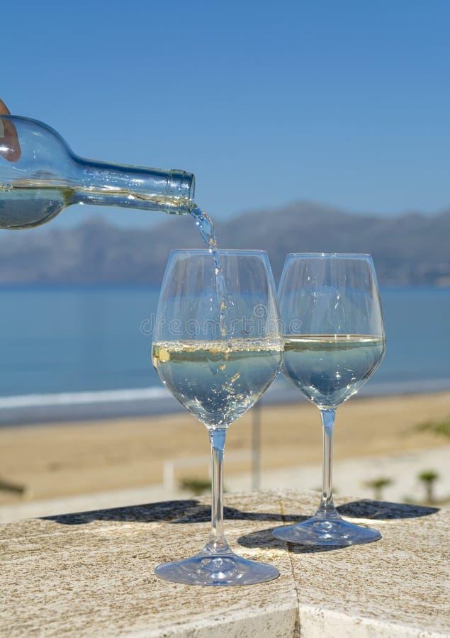 De kelner witte wijn in wijnglazen gieten op openluchtterras witn blauwe overzees en de bergen die bekijken op achtergrond royalty-vrije stock foto