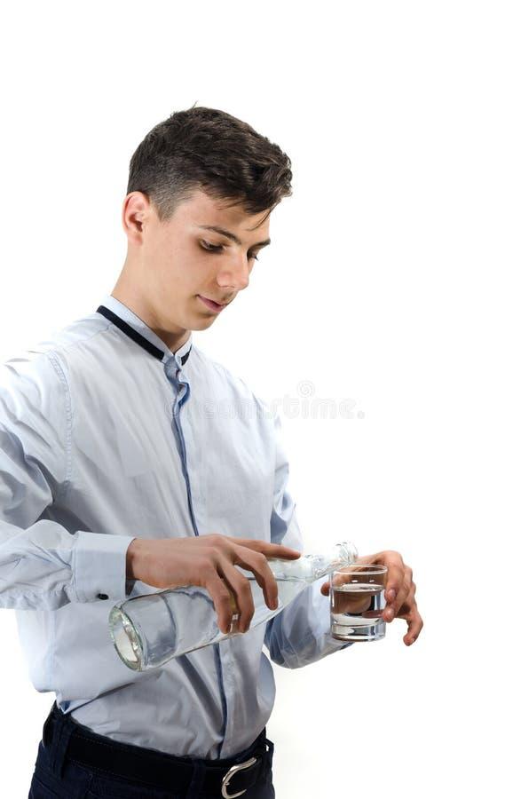 De kelners gietend water van de tienermens van glasfles in een glas stock afbeelding