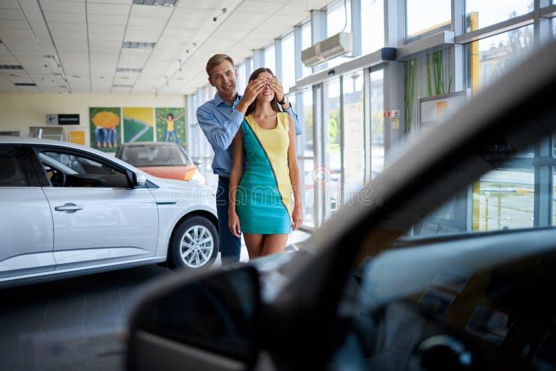De kerel bereidde een verrassing voor zijn meisje voor Het kopen van een nieuwe auto stock afbeelding