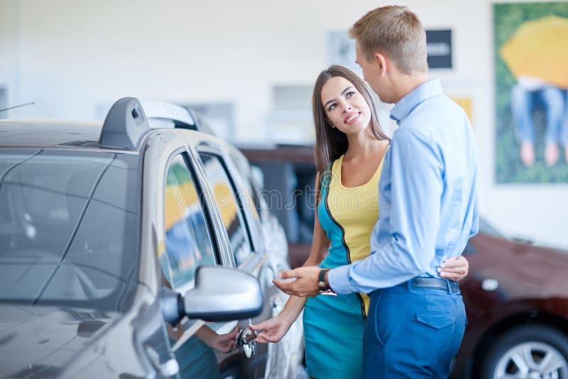 De kerel bereidde een verrassing voor zijn meisje voor Het kopen van een nieuwe auto stock afbeeldingen