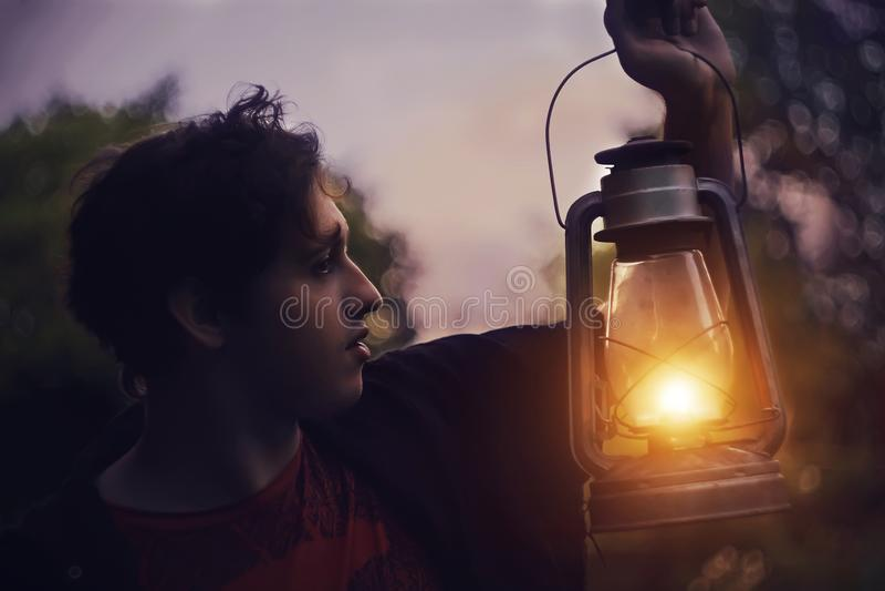 De kerel bevindt zich bij nacht in een bos met een aangestoken kerosinelamp stock afbeelding