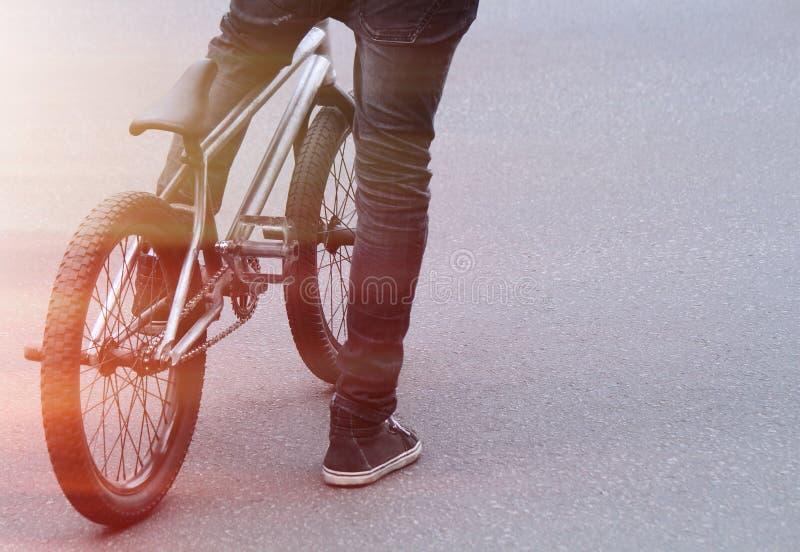 De kerel bevindt zich op het asfalt met een BMX-fiets stock foto's